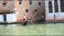 Gondolier steering through canal in Venice.