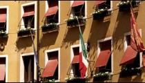 Windows and flags close up on side of building, Venice