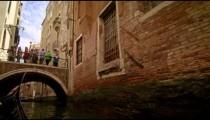 Gondola ride through a back alley canal toward a bridge