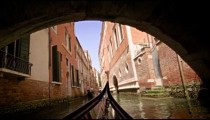 View from a gondola as it travels under a bridge in canal