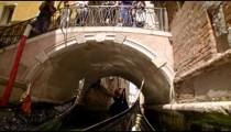 Gondola glides past other gondola's through and under a bridge