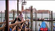 VENICE - MAY 2: A Gondolier waits on a dock on the Grand Canal on May 2, 2012 in Venice, Italy.
