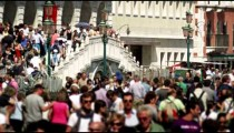 Slow motion shot of crowds walking across pedestrian bridge