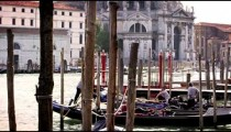 Docked gondolas and their gondoliers