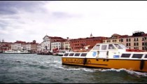 Tracking shot of Venice from a waterbus, approaching St. Mark's Basilica.