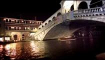 A single motor boat travels underneath the Rialto Bridge