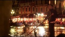 A gondolier paddles his boat on the Grand Canal at night
