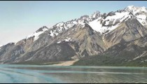 Time lapse of snowy mountains with blue sky background and glassy water in foreground, Alaska