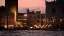 Static shot of boat passing in front of Piazza San Marco and the Doge's palace, mid evening.