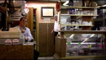 Static slow shot of three men working in an Italian cafe.