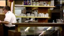 Static slow shot of food being put in refrigerator at an Italian cafe.