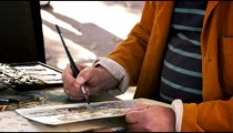 Shot of artist painting with watercolors in Venice.