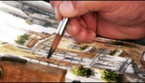 Close up shot of artist painting with watercolors a scene of a gondola on a canal in Venice.