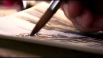Shot of an artist painting in details in a watercolor painting.