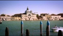 Panning shot of Giudecca across the canal from a marina.