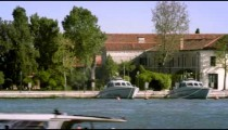 Tight panning shot of the east side of Giudecca from across the canal at a marina.