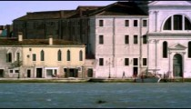 Tight panning shot of the Giudecca from across the canal at a marina.