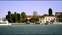 Tight static shot of the east side of Giudecca from across the canal at a marina.