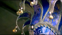 Close up tilting down shot of several elegant carnival masks blowing in the breeze.