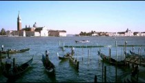 Shot of several gondolas in the canal with the island of San Giorgio.
