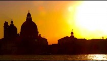 Slow motion, sun lens flare with Santa Maria della Salute in the setting sun.