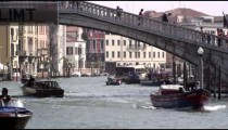 Slow motion shot of motor boats traversing the Grand Canal under the Ponte Scalzi bridge