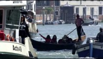 Slow motion shot of a gondolier navigating the busy Grand Canal amongst motor boats.