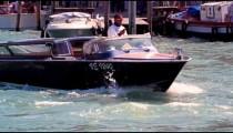 Slow motion shot of man driving black boat in venetian canal