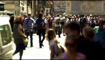 Slow motion footage of pedestrians and a car on a crowded street in Rome, Italy