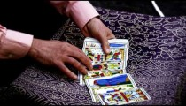 Slow motion shot of tarot card reading fanning cards on table