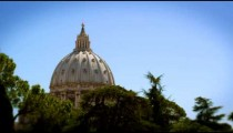 Shot of the Vatican dome from a distance looking through trees