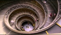 Tourists descend spiral stairs in slow motion