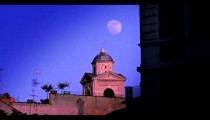 Moon behind small domed building