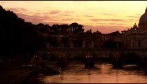 Left-to-right pan of Ponte Sant'Angelo and dome of St. Peter's Basilica at sunset