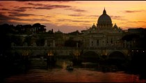 A boat travels under the Ponte Sant'Angelo at dusk. Dome of St. Peter's Basilica  in the background
