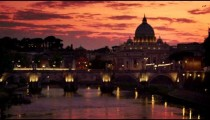 Racking focus of St. Peter's Basilica and Ponte Sant'Angelo at dusk