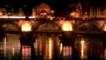 Left-to-right pan of illuminated Ponte Sant'Angelo at night