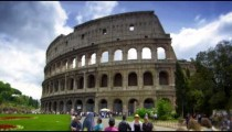 Pedestrians by gardens in front of The Colosseum in Rome Italy