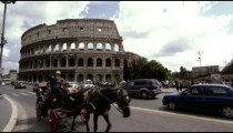 Horse carriage and automobile traffic in from of the Colosseum in Rome Italy
