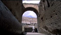 Slow motion footage of tourists walking by an arch in the stands of the Colosseum