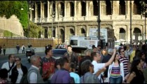 Slow motion shot of Colosseum with traffic and crowd