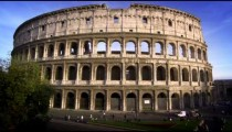 Slow motion upward tilt shot from the street to the Colosseum