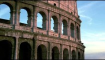 Upward tilt of Roman Colosseum and Arch of Constantine in evening