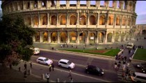 Cars and buses on street in front of Colosseum and Constantine's Arch