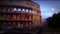 Tilt up from street to illuminated Colosseum at night