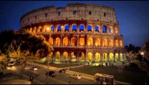Tilt up from intersection to illuminated Colosseum