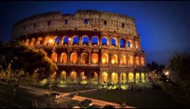 Left-to-right pan of intersection and Colosseum at night