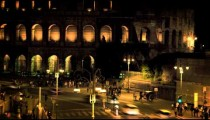 Vehicles and pedestrians in front of Colosseum at night