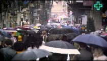 Overly crowded street in Rome, filled with umbrellas.
