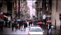 Slow motion footage of people walking down a wet roman street